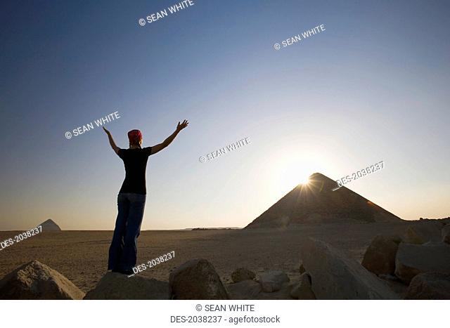 A Young Woman Tourist Raises Her Arms Toward The Sun And The Red Pyramid, Dashur Egypt