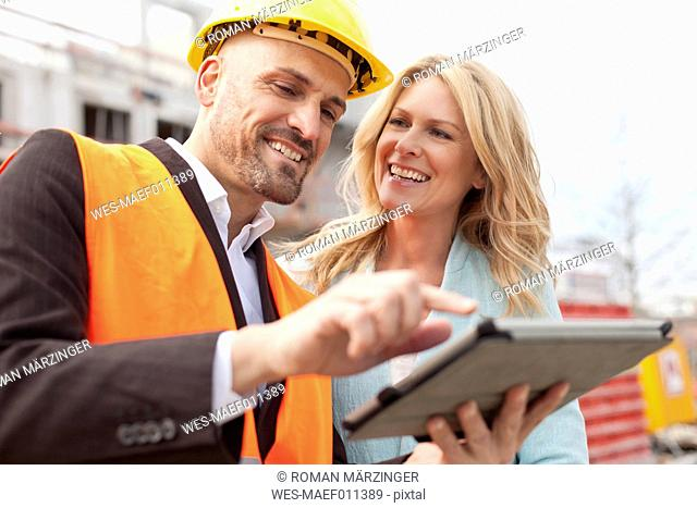 Smiling man with hard hat talking to woman on construction site