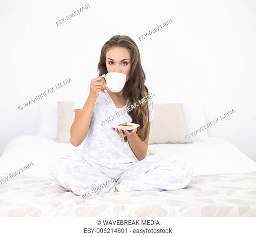 Content attractive brunette drinking from a cup