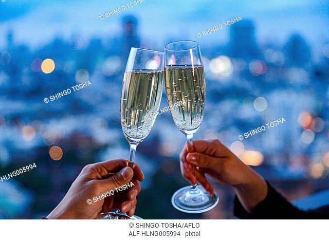 Toasting with champagne in front of Tokyo cityscape