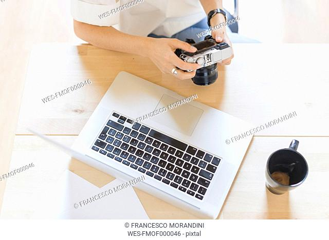 Woman sitting at desk with laptop and coffee cup holding digital camera, partial view