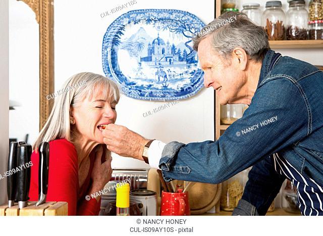 Man feeding wife in kitchen