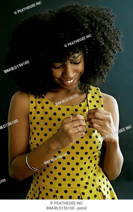 Close up of mixed race woman playing with her curly hair