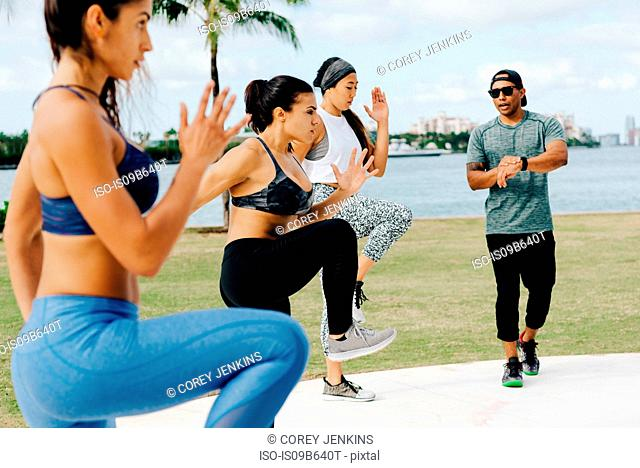Three women working out with personal trainer, South Point Park, Miami Beach, Florida, USA