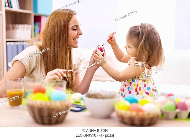 Happy mother helping baby painting on easter eggs. Debica, Poland