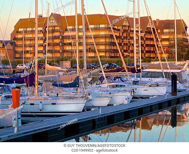 Port Deauville, Floating quay, and pleasance boats moored, with contemporary flats in norman style, in the background, sea front, at sunset, Deauville, Calvados