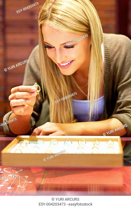 Lovely young woman choosing a ring from a tray in front of her