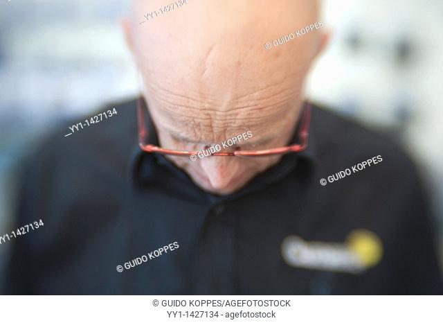 Rotterdam, Netherlands. Bald man wearing glasses working in a store serving a customer