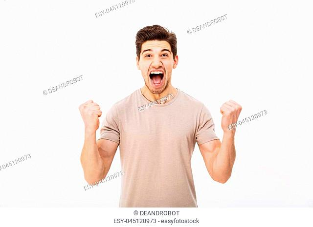 Photo of delighted brunette guy shouting and clenching fists like winner or lucky person isolated over white background