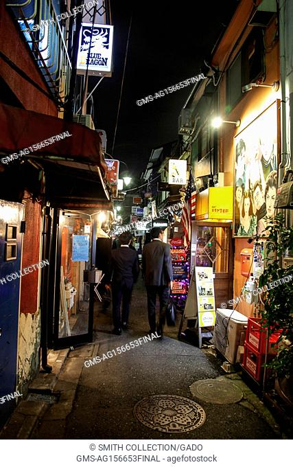 Salarymen in suits walk through the Golden Gai neighborhood of Shinjuku, an area known for its vibrant night life and bar scene, Tokyo, Japan, October 24, 2017