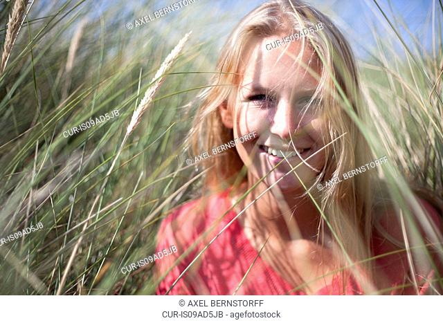 Portrait of blonde woman in marram grass, Wales, UK