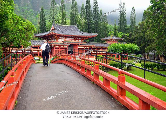 A senior man walks towards a Buddhist Temple