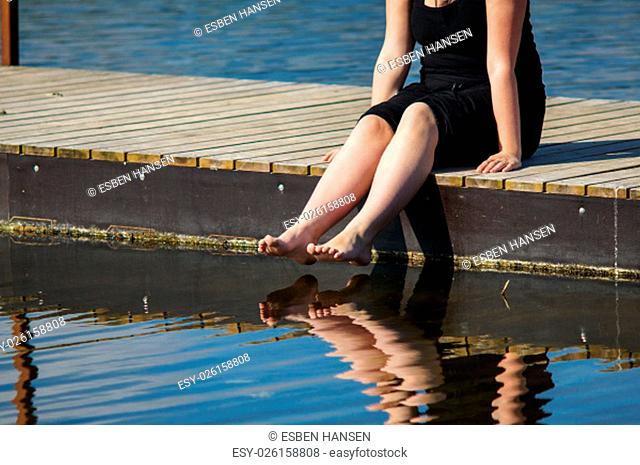 Young women sitting on the Jetty, with jer legs in the lake water