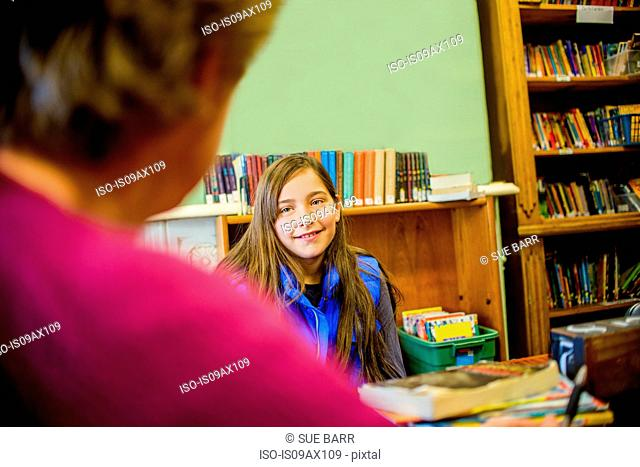 Teenage girl in school speaking to guidance counselor smiling