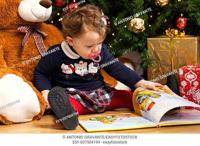 Beautiful toddler baby girl reading fairy tales near gifts and christmas tree