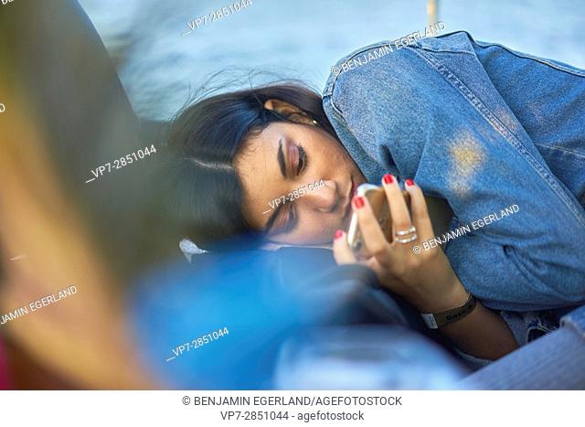 Concentrated young woman using mobile device while relaxing in bar next to sea