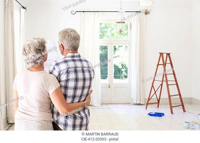 Older couple looking at construction plans together