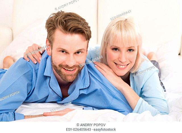 Happy Young Couple Lying On Bed In Bedroom At Home