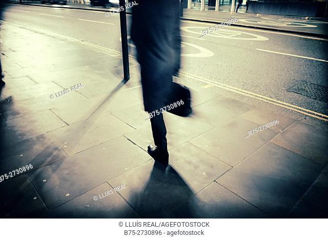 Unrecognizable businessman with portfolio walking down in the street in the city of London, England