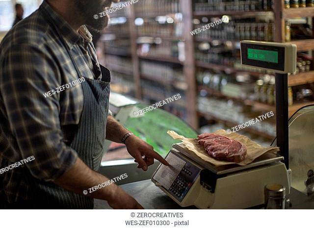 Butcher weighing meat on scale