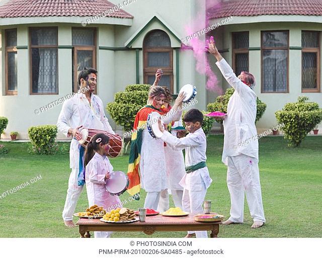 Family dancing and celebrating Holi