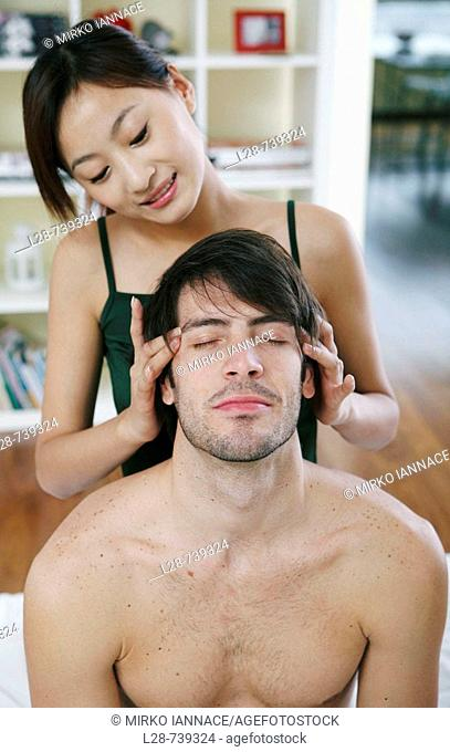 Young woman giving a young man a head massage