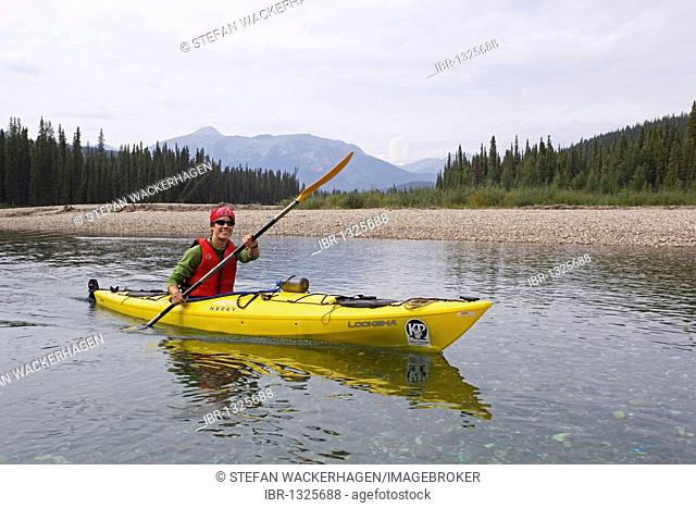Young woman in kayak, paddling, kayaking, clear, shallow water of upper Liard River, Pelly Mountains behind, Yukon Territory, Canada