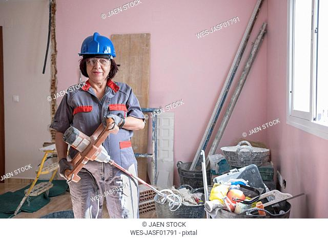 Senior woman with paint mixer at construction site