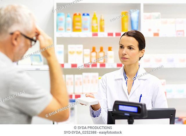 apothecary giving drug to senior man at pharmacy