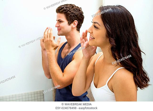 Young couple applying cream on face while looking in mirror