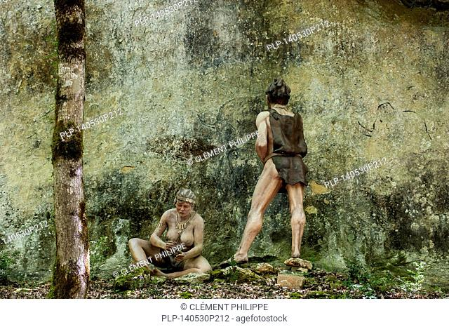 Diorama showing Cro-Magnon woman and man painting animals on rock face at Prehisto Parc, theme park about prehistoric life at Tursac, Périgord, Dordogne, France