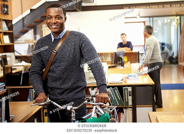 Architect Arrives At Work On Bike Pushing It Through Office