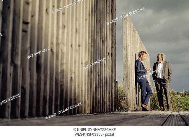 Two businessmen standing on boardwalk talking