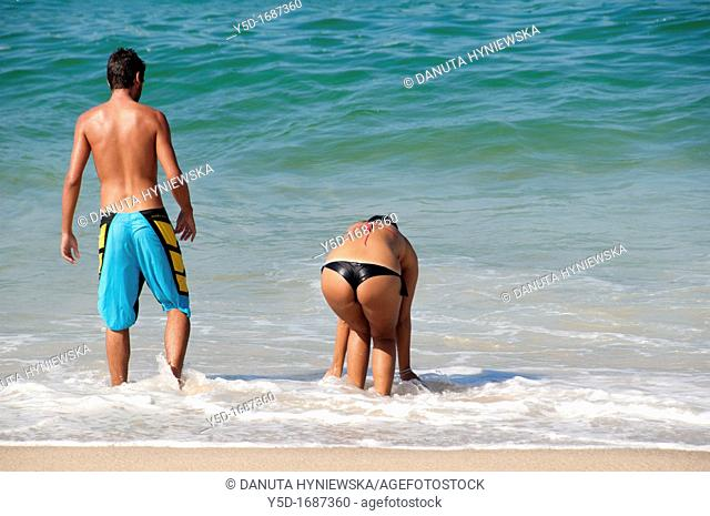 Young couple entering the water of Atlantic Ocean, Portugal, Silver Coast, May