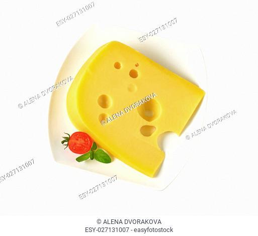 wedge of medium-hard Swiss cheese on white plate