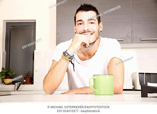 A young man sitting in the kitchen and drinking coffee