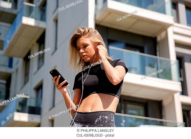 Young woman listening to music on mobile phone, building in background