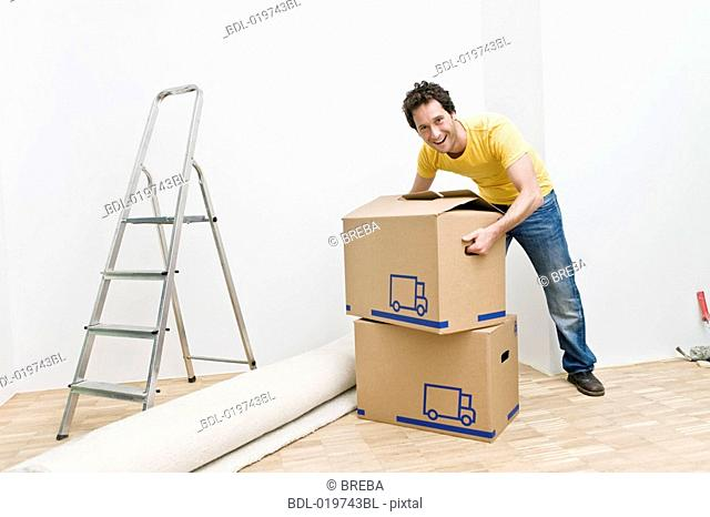 full body portrait of young man with moving boxes in his new home