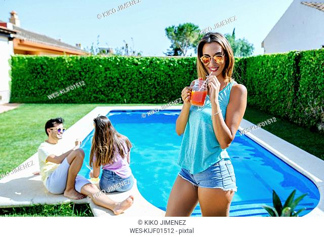 Woman holding drink at the poolside with friends in background