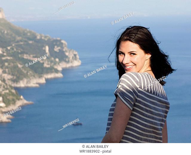 Italy, Ravello, Palazzo Sasso, Portrait of smiling woman with coastline in background