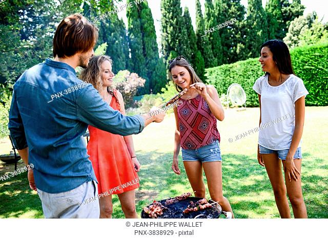 Groupe of happy and cheerful young people having fun around barbecue grill during summer holiday party outdoor in the garden