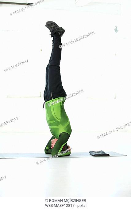 Man doing his fitness regime, practising headstand