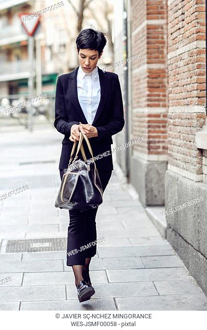 Portrait of young businesswoman with bag walking on pavement