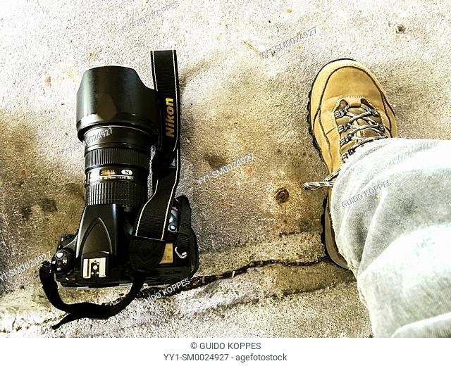 Coevorden, Netherlands. A male's right leg and foot inside a hiking shoe alongside a camera on the concrete floor of a mill