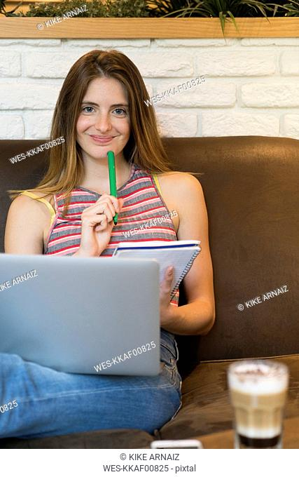 Young woman with notepad and laptop in a cafe