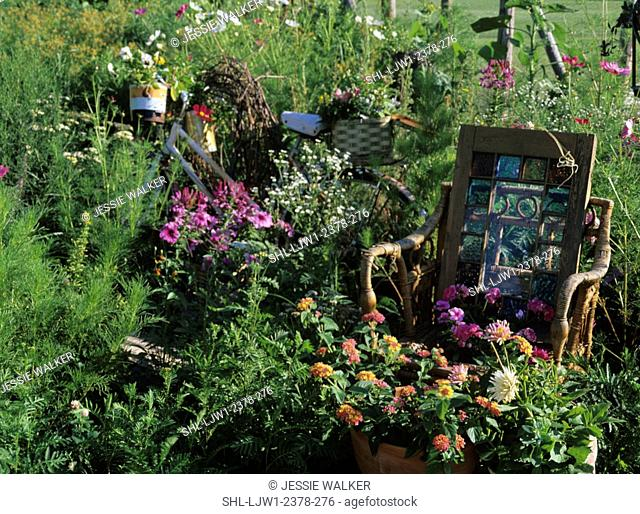 Gardens: Whimsical garden of household items, wicker chair, stained glass window, potted plants at foot of chair, rusting bike