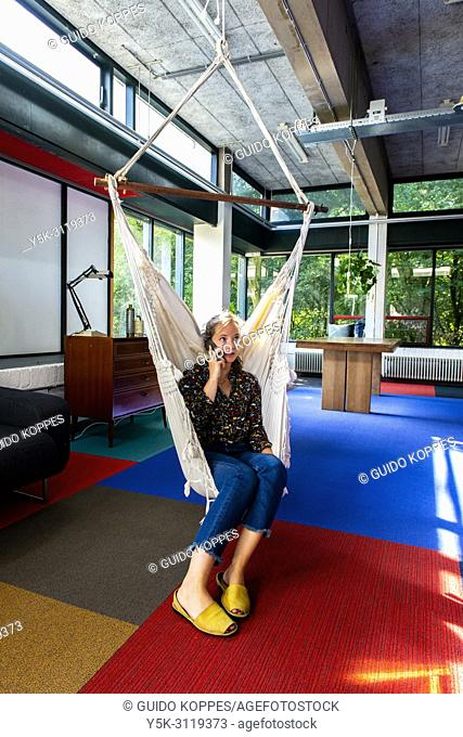 Amsterdam, Netherlands. Young, female freelance journalist hanging out in an office hammock, while engaging in a tele conversation using her smartphone