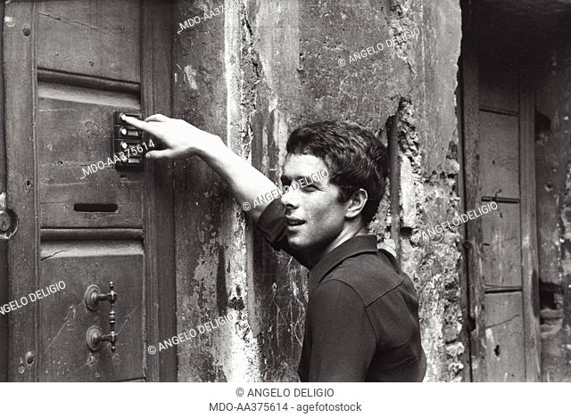 Gabriele Lavia calling on the entryphone. Italian actor Gabriele Lavia calling on the entryphone of a door. Rome, 1970s