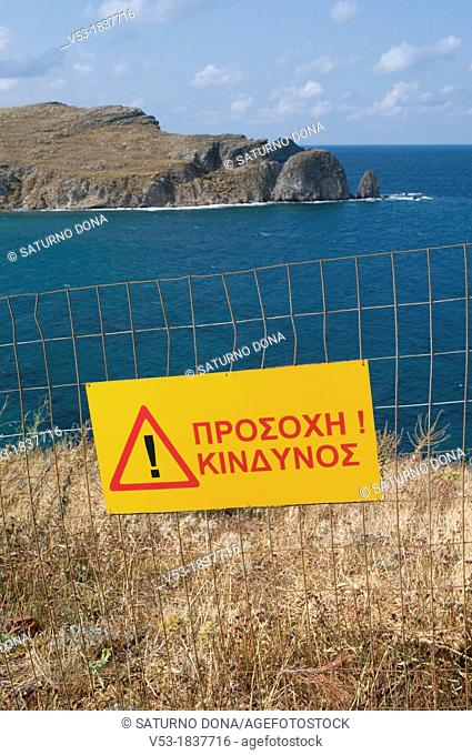 Warning sign and protection net by the cliff, Lemnos, Greece