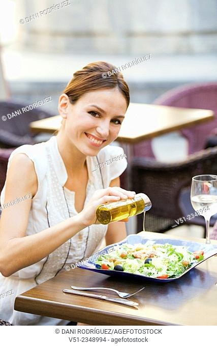 Pretty woman enjoying a salad in a restaurant outdoors smiling at camera